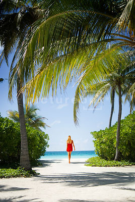 An atmospheric image of a woman in a red beachware walking on a tropical beach.