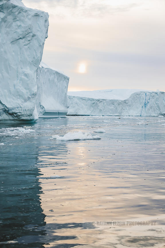 Icebergs in oily smooth water bathing in morning sunlight in Ilulissat, Greenland