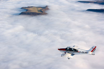 Small Aeroplane flying above clouds at an airfied on the Farrenberg, Baden-Wuerttemberg, Germany