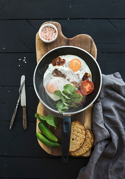 Pan of fried eggs, bacon, tomatoes with bread, greens and cucumbers on rustic wooden serving board over dark table surface