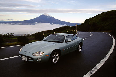 A Jaguar sports car on a road with Mount Fuji in the background, Hakone, Japan