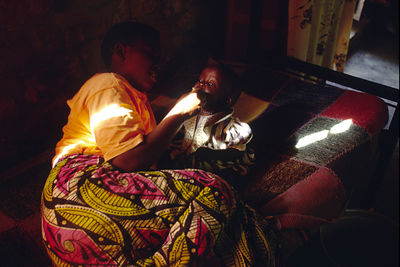 Burundi - Ruyigi - Martine, 1 year old with AIDS, sits in a shaft of sunlight after being fed by Gloria, another orphan