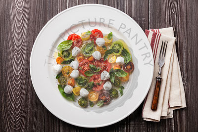 Ripe fresh colorful tomatoes salad with basil and mozarella mini on gray wooden background