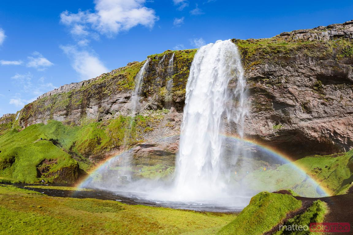 Seljalandsfoss waterfall with rainbow in summer, Iceland