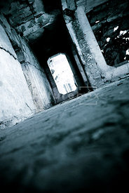 An atmospheric image of a door in a decaying concrete bunker.