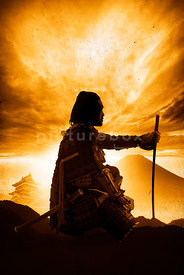 An atmospheric image of the silhouette of a crouching Samurai Warrior at dawn.