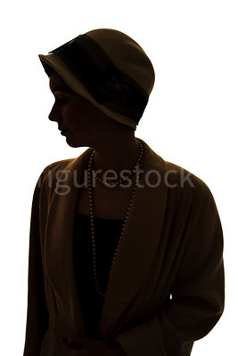A silhouette of a vintage 1920s - 1930s woman in a hat and coat – shot from eye level.