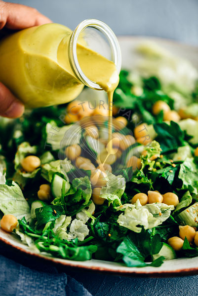 A woman pouring turmeric tahini dressing over a bowl of green salad with chickpeas.