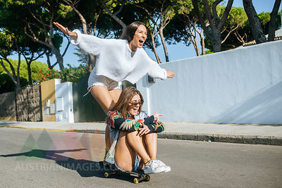 Two laughing friends together on skateboard