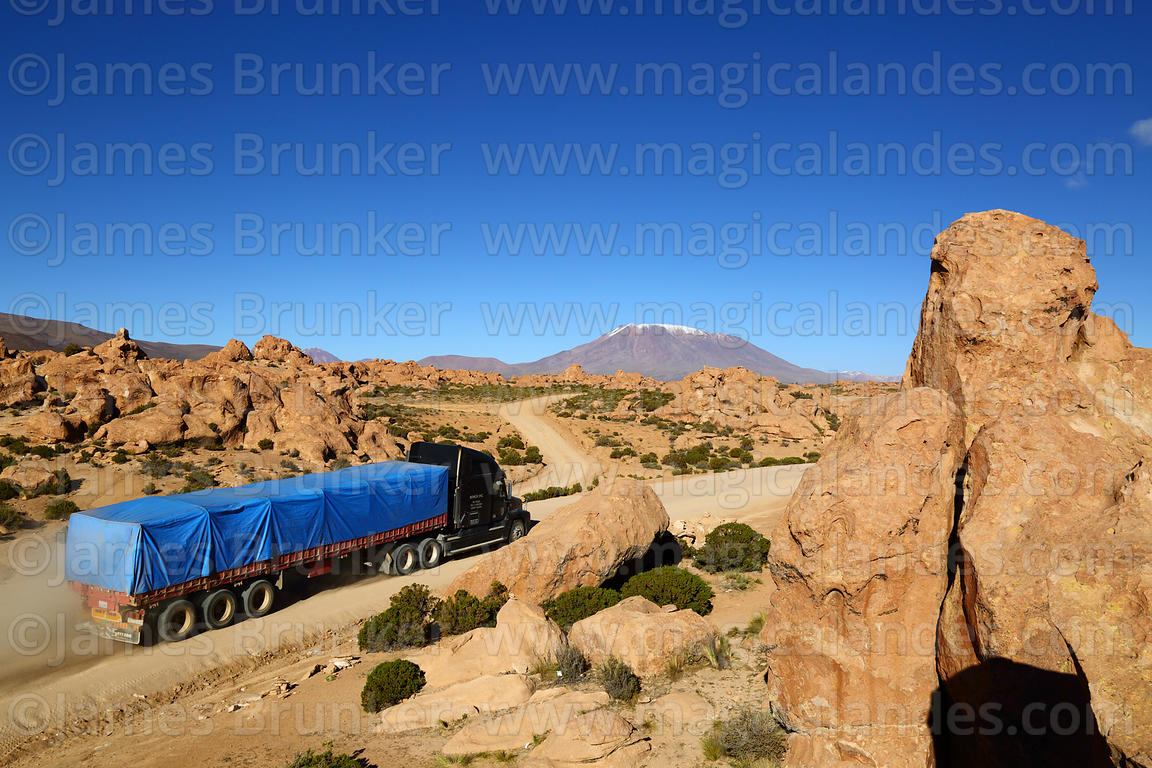 Truck on Route 701 driving past eroded volcanic rock formations, Cerro Caquella volcano in background, Nor Lípez Province, Bo...
