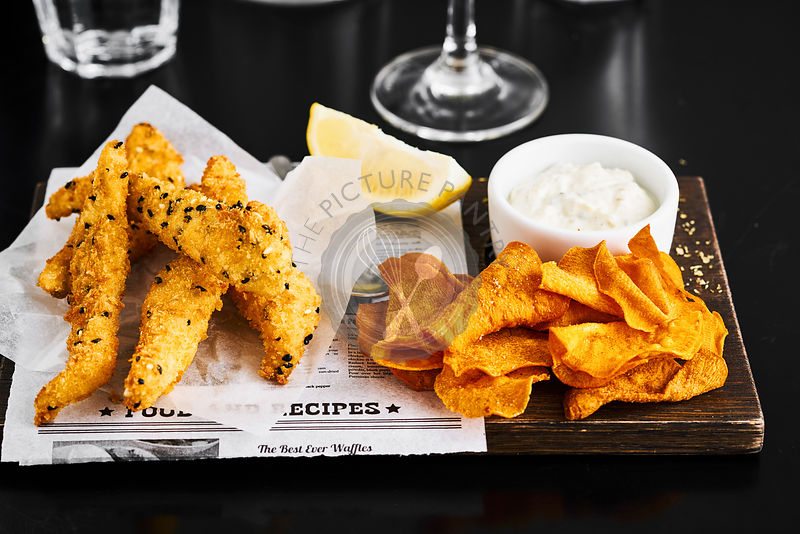Fish and chips on a rustic wooden board