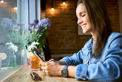 Smiling young woman using phone in cafe