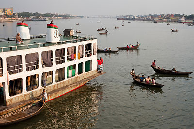 Bangladesh - Dhaka - A man offers prayers on the roof of a ferry in Sadarghat whilst river taxis ply their trade