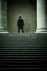 An atmospheric image of a mystery man in a hat, standing at the top of some steps in an old temple.