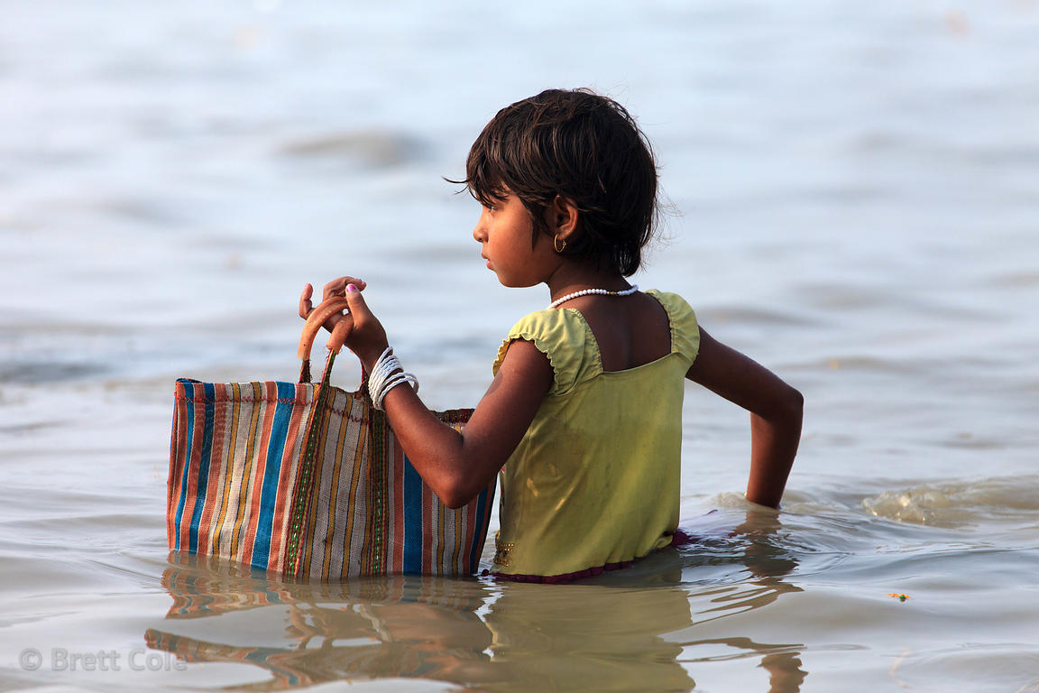 A girl collects discarded coconuts in the Bay of Bengal at the Gangasagar Mela (festival), a pilgrimage to Sagar Island in In...