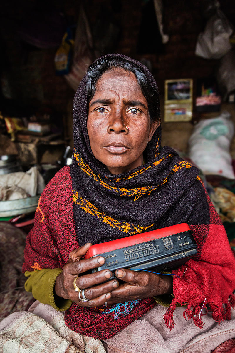 Woman at Streetside Shanty Holding a Radio