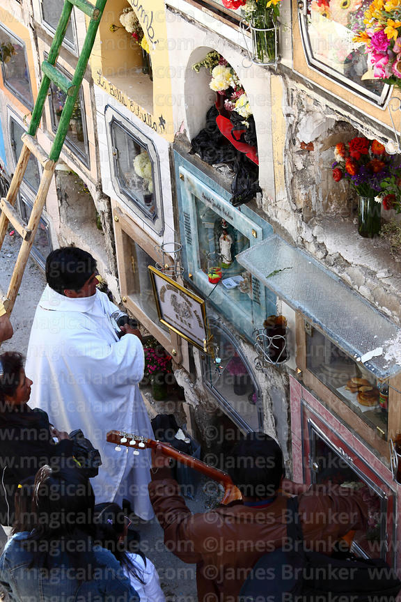 Priest praying during farewell ceremonies for souls of the deceased in cemetery, Todos Santos festival, La Paz, Bolivia