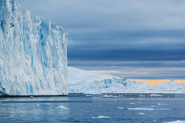 So many icebergs in the Ilulissat Icefjord, with an orange strip of sky appearing close to the horizon