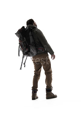 A man in outdoor clothing with a backpack, from behind, in semi-silhouette – shot from low level.