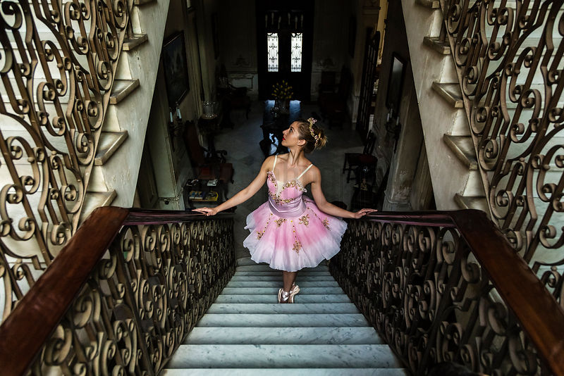 Ballerina in Traditional Tutu on the Stairs of a Pre-Revolutiuonary Colonial Home