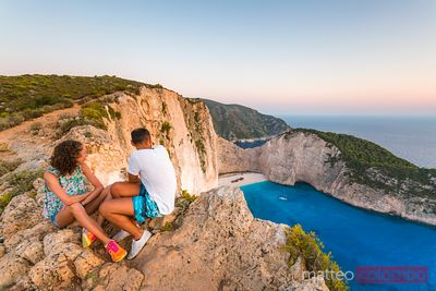 Couple of tourists on cliff edge over shipwreck beach at sunset. Zante,  Greece