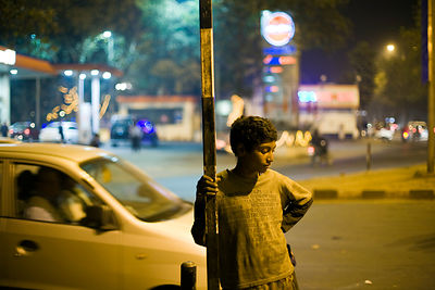 India - New Delhi - Durga, 12 waits by the side of the road while his sister begs from passing motorists