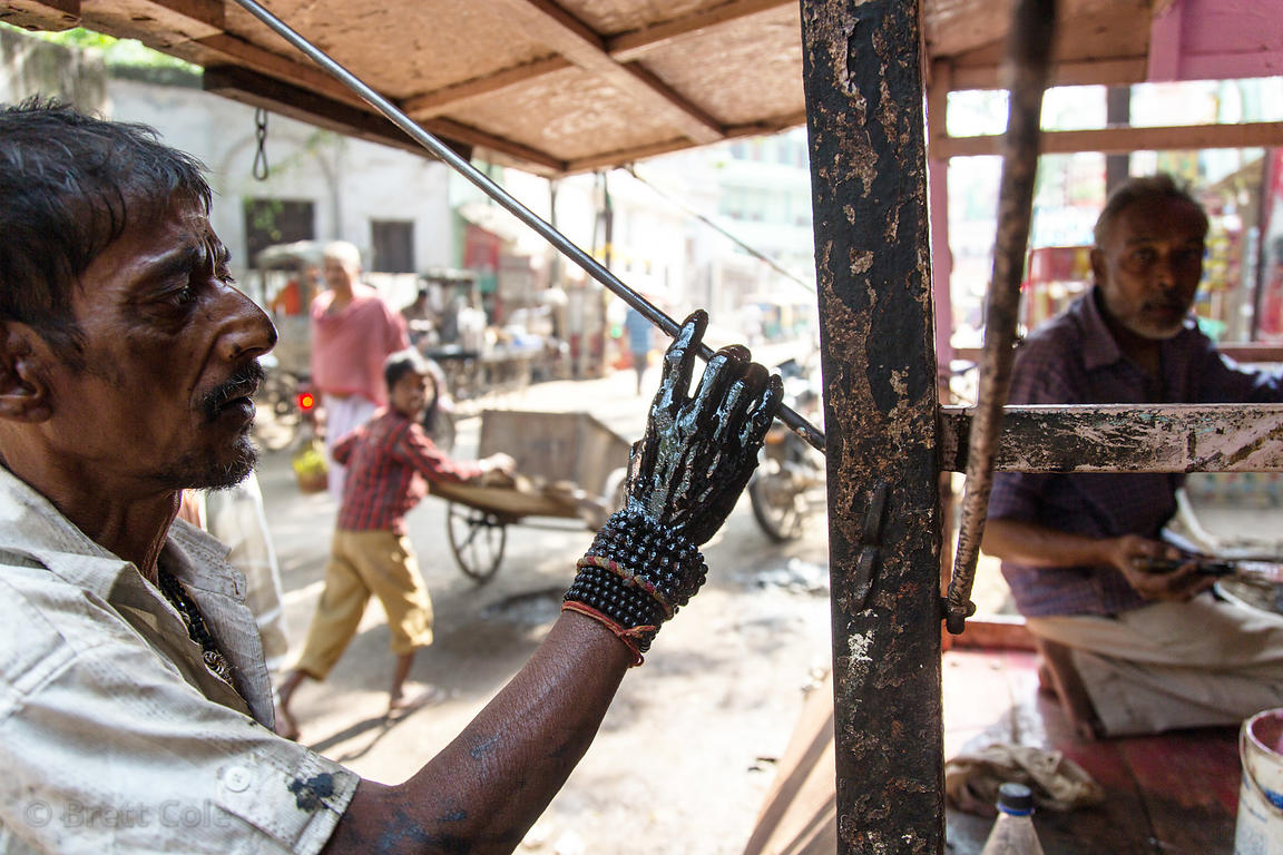 A mechanic work with motor oil, Birdopur, Varanasi, India