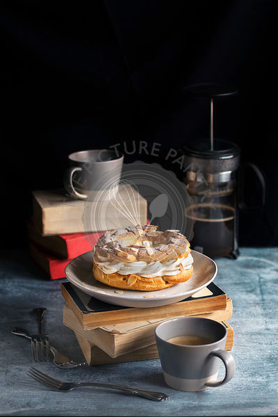 French paris-brest pastry,coffee mugs and french coffee pot on the table