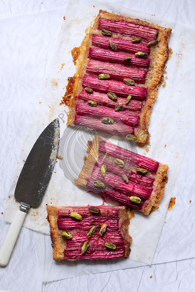 A rhubarb and pistachio nut tart on baking paper with a knife.