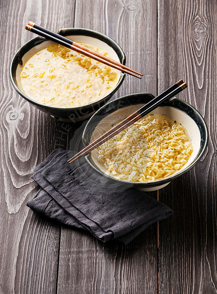 Asian Miso ramen noodles and chopsticks in bowls on gray wooden background