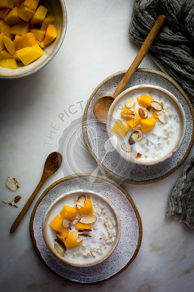 Breakfast Oatmeal porridge with milk topped with chopped mangoes and almonds in a ceramic bowl on a marble table on top view