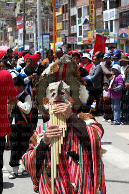 Kusillo wearing leather mask and poncho playing panpipes at Virgen de la Candelaria festival, Puno, Peru