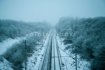 An atmospheric image of a frozon snow and Ice covered landscape with a train tracks going into the distance, in Northamptonsh...
