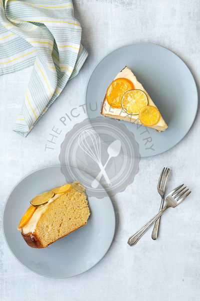 Two slices of orange cake on plates with cake forks.