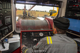 Man in wireline truck lowers bottom hole assembly in an oil well