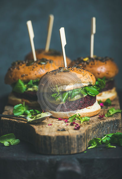 Healthy vegan burger with beetroot and quinoa patty, arugula, avocado sauce and wholegrain buns on rustic wooden board