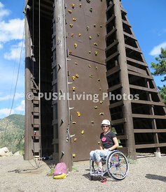 Young woman in a wheelchair at a rock climbing wall