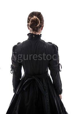 A Victorian woman, in a dress, looking away – shot from eye level.