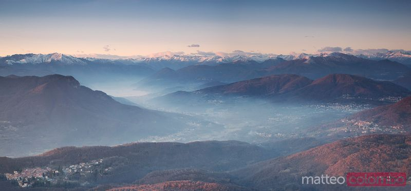 Valleys in the mist and the italian alps at sunset