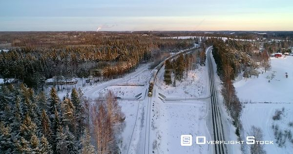 Train on a Winter Countryside, Aerial, Reverse, Drone Shot, Following a Cargo Locomotive, at Sunset, in Scandinavian Nature, ...