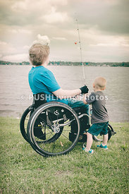 Young man in a wheelchair with a young child by the lake fishing
