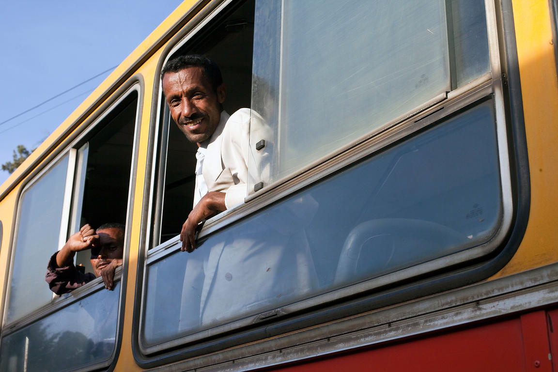 Ethiopia - Addis Ababa - Two men looking out from a public bus in the Piazza district