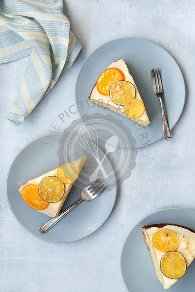 Slices of iced orange cake on plates with forks.