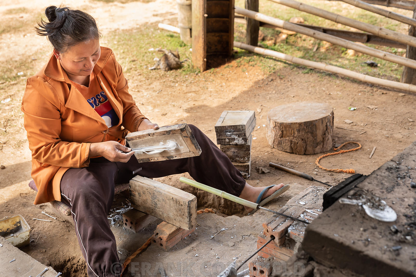 "PHONSOVAN, LAOS - JANUARY 29, 2019: A woman making ""war spoons"" in Laos.  Locals make cutlery and jewellery using scrap alumi..."