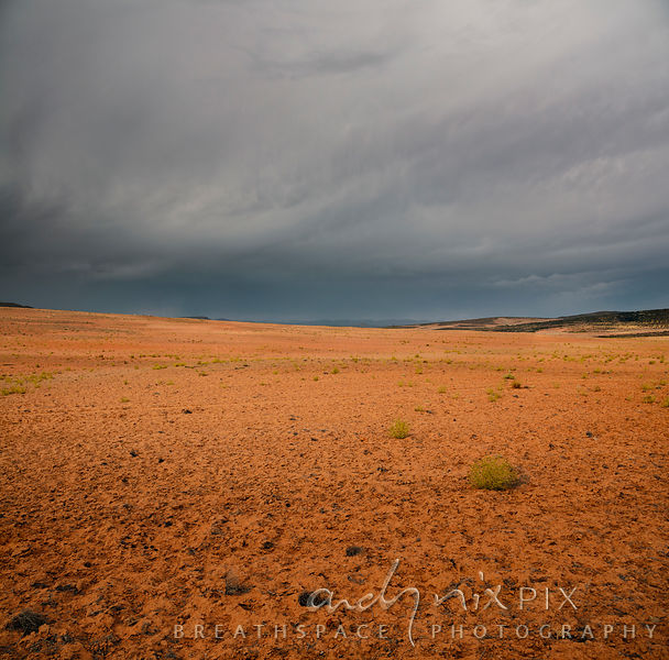 Dry red sandy desert under dark stromy sky