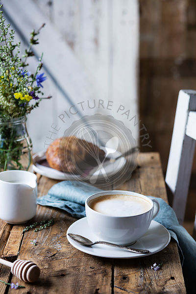 Breakfast table: cappuccino and croissant on wooden rustic table