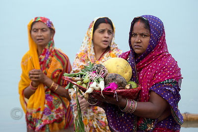 Women make offerings on the Ganges River during Chhath Puja, Varanasi, India. Chhath Puja is a devotion to the Sun God Surya ...