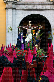 Penitents carrying statue of Jesus on the cross / Paso del Calvario out of La Merced church at start of Good Friday processio...