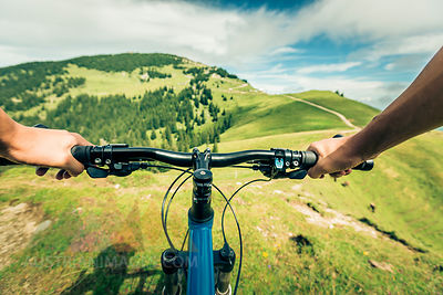 Germany, Bavaria, Pfronten, mountainbiker riding downhill on alpine meadow near Aggenstein