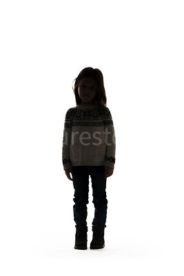 A silhouette of a little girl standing, facing forward – shot from mid level.